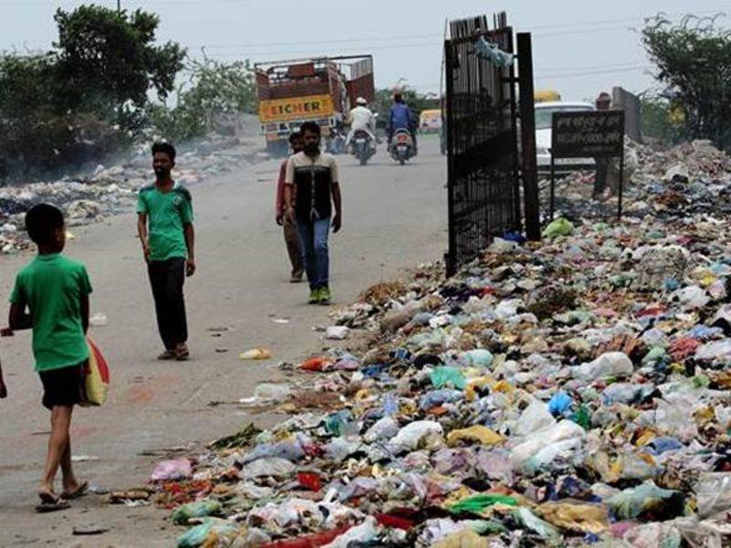Children walk by the garbage dump site.